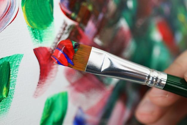 Pędzel z wielokolorowymi farbami na tle obrazu