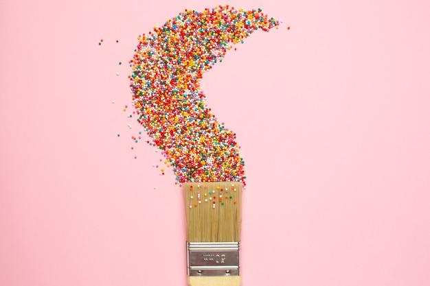 Pędzelek i wielokolorowe okrągłe konfetti na cukierki