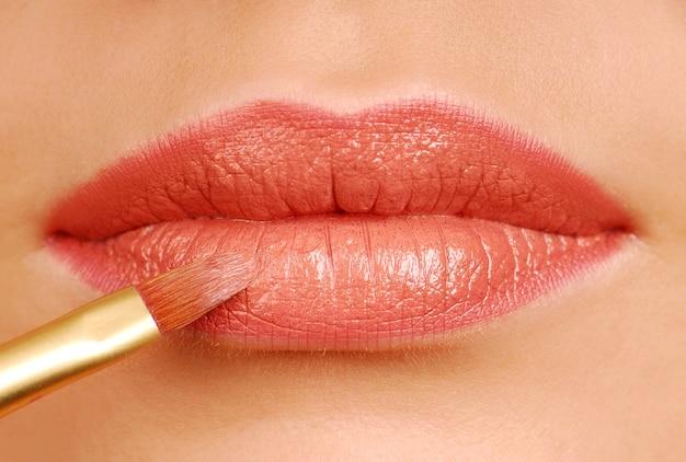 Pędzelek kosmetyczny czerwona szminka. narzędzie do makijażu. usta kobiety z bliska.