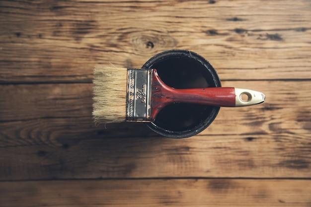 Pędzelkiem na miskę z farbą na drewnianym stole