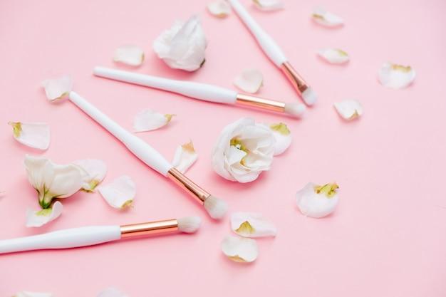 Pędzle do makijażu i kwiaty na różowo