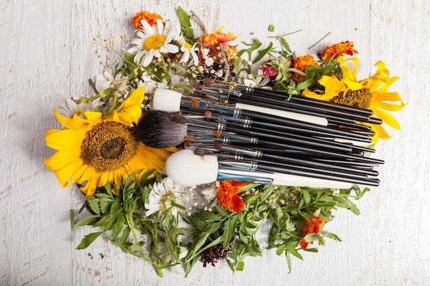 Pędzle do makijażu na stosie dzikich kwiatów na drewnianym tle