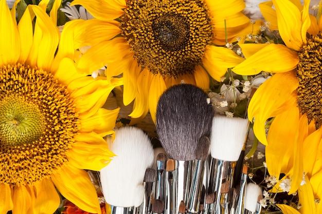 Pędzle do makijażu obok pięknych dzikich kwiatów na drewnianym tle