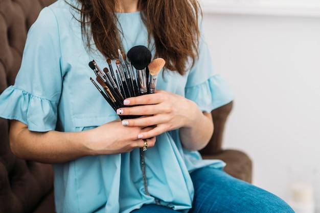 Pędzle do makijażu w rękach pięknej młodej stylowej kobiety