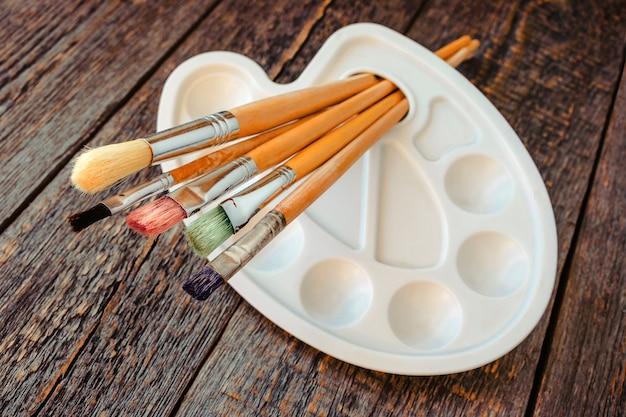 Pędzle do malowania i palety leżące na starym drewnianym stole
