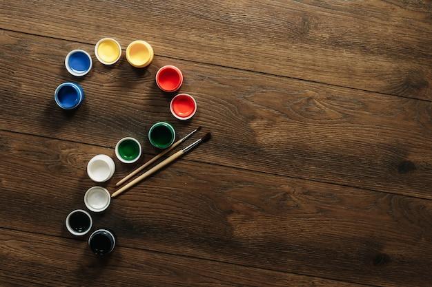 Pędzle i farba otwarta na brązowym drewnianym stole