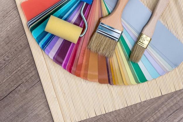 Pędzle malarskie na próbce koloru na drewnianym stole