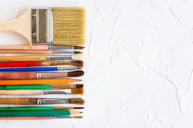 Pędzle o różnych rozmiarach i ołówki na białym tle tekstury obiekt sztuki i edukacji