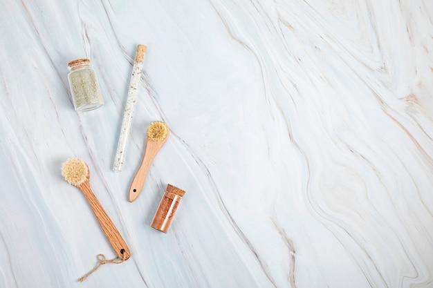 Pędzle z naturalnego włosia, sól do kąpieli i maski z glinki w szklanych słoikach na tle białego marmuru. koncepcja spa, samoopieki i odnowy biologicznej. widok płaski, widok z góry