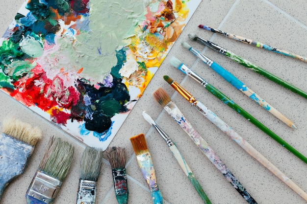 Pędzle z paletą w kreatywnej kompozycji. kolorowy element