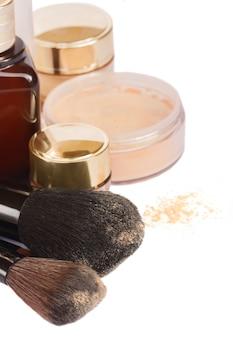Pędzle z podstawowymi produktami do makijażu na białym tle