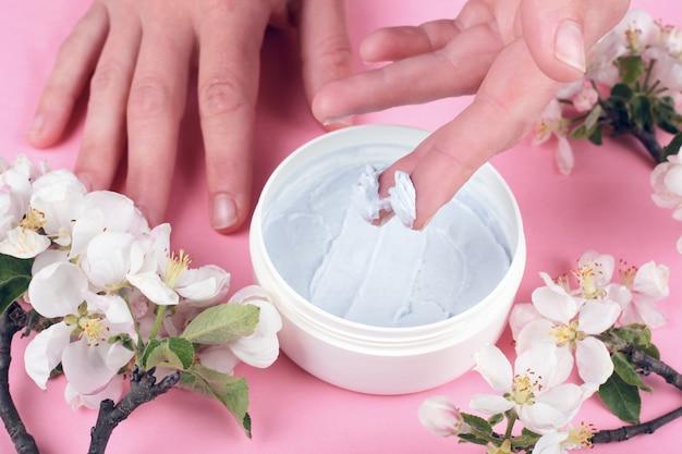 Peeling do ciała na różowym tle z białymi kwiatami jabłka, dłonie nakładające peeling z bliska, pielęgnacja skóry, uroda, spa