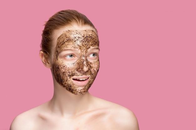 Peeling do skóry twarzy. portret seksowny uśmiechający się modelki stosowania naturalnej maski do kawy, peeling twarzy na skórze twarzy. zbliżenie piękna szczęśliwa kobieta z twarzą zakrywającą piękno produktem.
