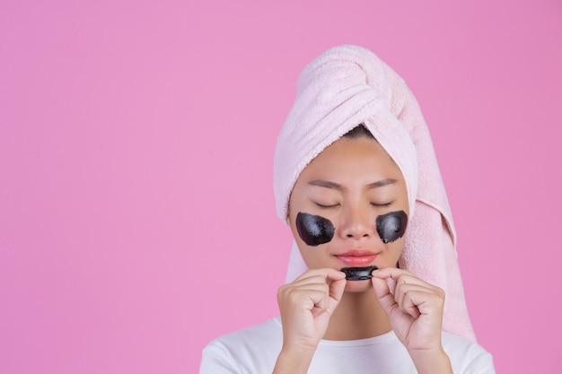 Peeling kosmetyczny. młoda suczka z czarną maską peel off na skórze kosmetyk złuszczający produkt do twarzy na różowo
