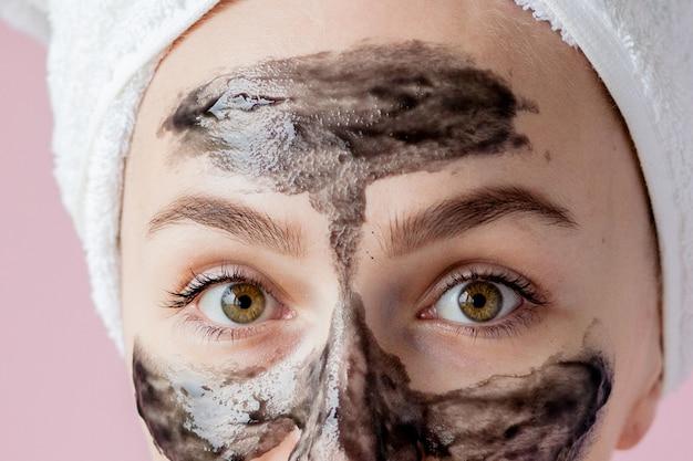 Peeling kosmetyczny. zbliżenie piękna młoda kobieta z czarną odkleić maskę na skórze