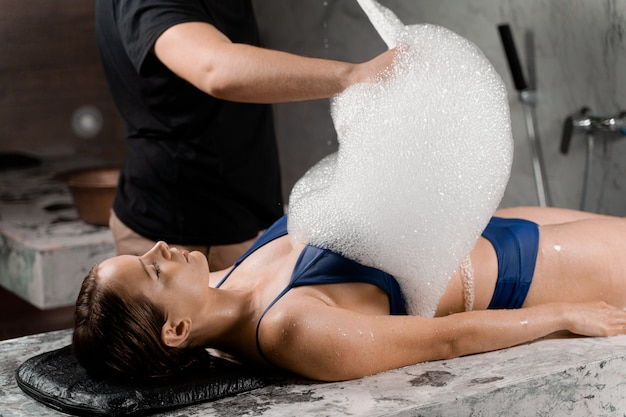 Peeling piankowy w spa. kobieta leży na plecach i relaksuje. procedura tureckiego hammamu.