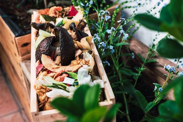 Peelingi i odpady organiczne w drewnianej skrzyni do tworzenia domowego kompostu.