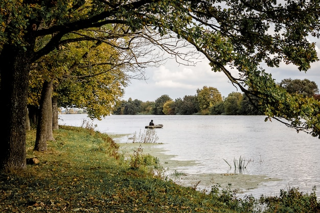 Peizaz z rzeką i lasem. drzewa nad wodą. rybak w łodzi na środku rzeki