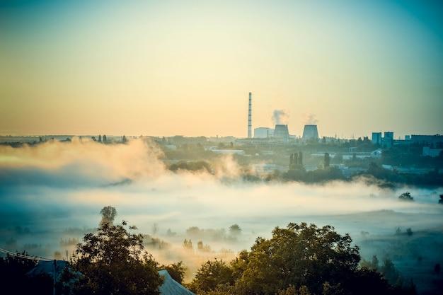 Pejzaż elektrowni i pole z mgłą