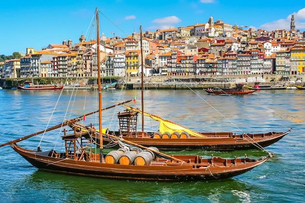 Pejzaż miasta porto, rzeka douro ze starą łodzią i typowymi kolorowymi domami na brzegu. portugalia. europa.