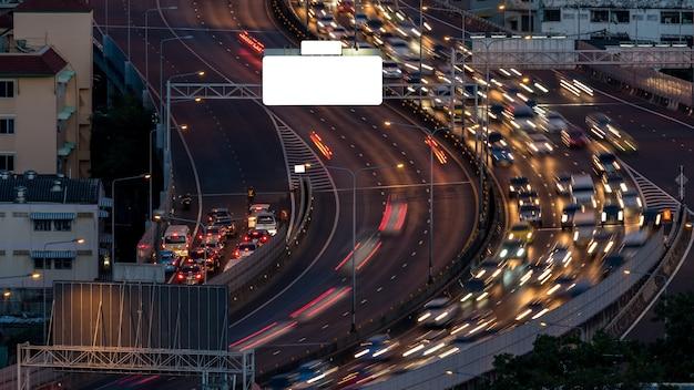 Pejzaż miejski i światło nocy droga w długim ujawnieniu z billboardem od drapacza chmur