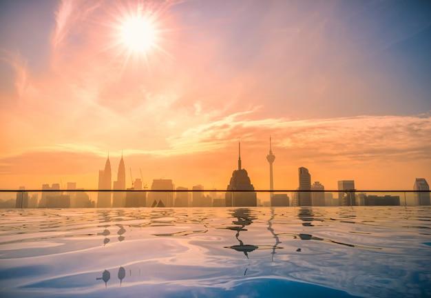 Pejzaż miejski kuala lumpur miasta linia horyzontu z pływackim basenem na dachu wierzchołku hotel przy wschodem słońca w malezja.