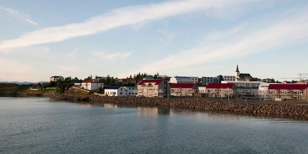 Pejzaż miejski, mieszkania i wieża na brzeg rzeki