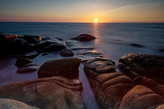 Pejzaż morski o zachodzie słońca z fal morskich ruchu przez łuk z kamienia naturalnego z odbicia światła na wodzie ruchu w larn hin kaw, rayong, tajlandia. znany cel podróży lub wczasowicz w tropikalnym kraju