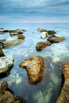 Pejzaż morski przyrody morza i kamieni w wodorostach podczas zachodu słońca
