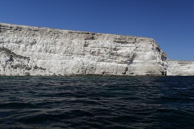 Pejzaż morski, wysokie skaliste wybrzeże i ciemnoniebieska powierzchnia wody morza.