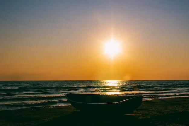 Pejzaż morski z łodzią na brzegu przed zachodem słońca