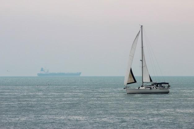 Pejzaż morski z widokiem na jacht z żaglami i statek towarowy na horyzoncie