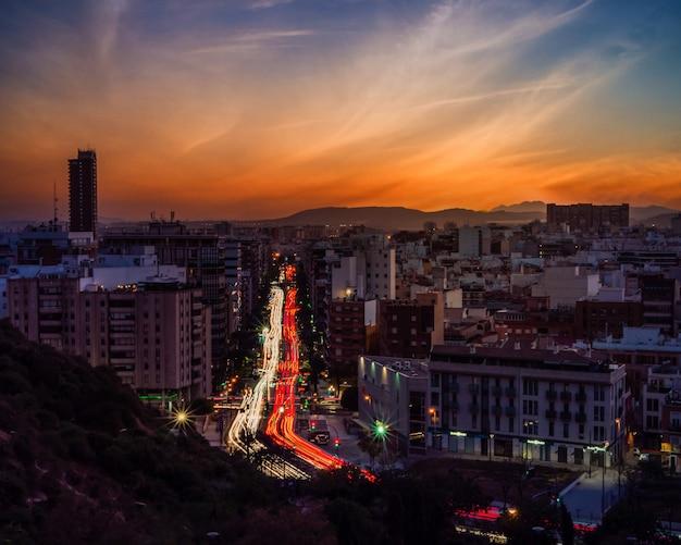 Pejzaż nowoczesnego miasta otoczony światłami z długą ekspozycją podczas pięknego zachodu słońca
