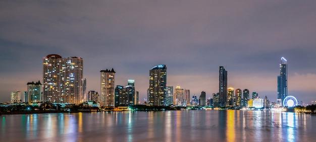 Pejzaż nowoczesny budynek w pobliżu rzeki w nocy. nowoczesny budynek biurowy. drapacz chmur z wieczornym niebem. nocna fotografia budynku nad brzegiem rzeki.