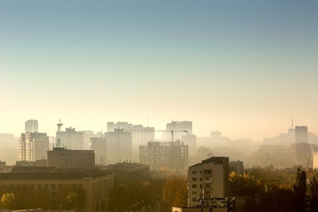 Pejzaż o wschodzie słońca, dachy budynków, dźwigi budowlane.