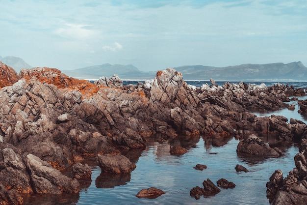 Pejzaż strzał dużych skał na brzegu morza z zachmurzonym niebem i górami