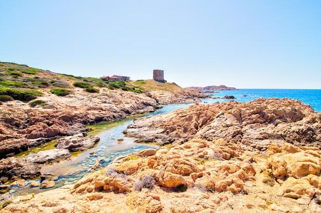 Pejzaż strzał skalistych wzgórz z budynkiem zamku w pobliżu otwartego morza z jasnym słonecznym błękitnym niebem