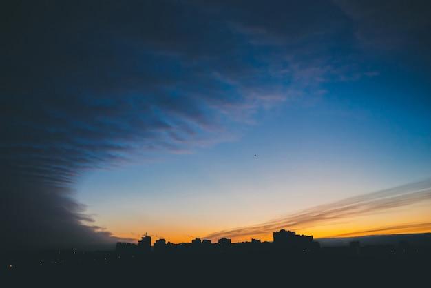 Pejzaż z cudownym, barwnym, barwnym świtem niesamowite dramatyczne błękitne niebo nad ciemnymi sylwetkami dachów budynków miasta.