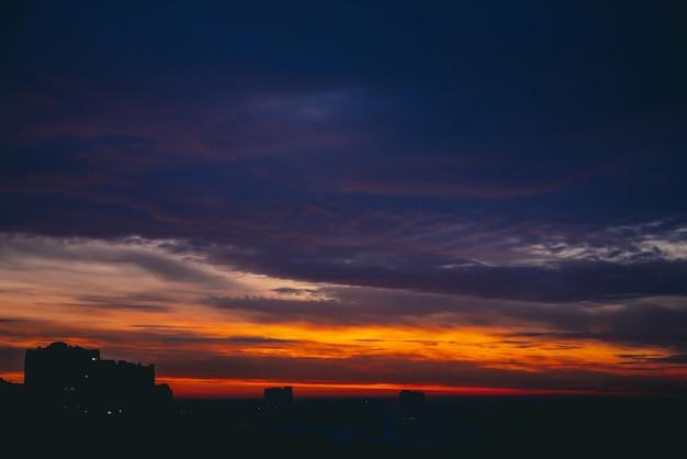 Pejzaż z cudownym, barwnym, ognistym świtem. niesamowite dramatyczne wielokolorowe pochmurne niebo. ciemne sylwetki dachów budynków miasta. atmosferyczne tło wschodu słońca w pochmurnej pogodzie. skopiuj miejsce