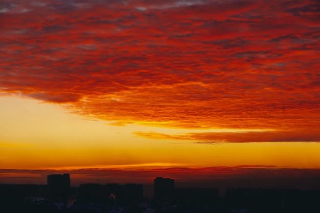 Pejzaż z świtem ognistej krwi wampira. niesamowite ciepłe dramatyczne pochmurne niebo nad ciemnymi sylwetkami budynków miejskich. pomarańczowe światło słoneczne. atmosferyczne tło wschodu słońca w pochmurnej pogodzie. skopiuj miejsce