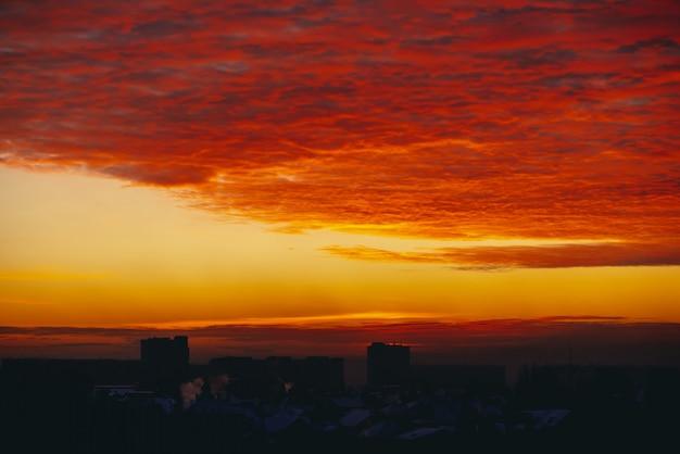 Pejzaż z świtem wampirów krwi. niesamowite ciepłe dramatyczne pochmurne niebo nad ciemnymi sylwetkami budynków miejskich. pomarańczowe światło słoneczne.