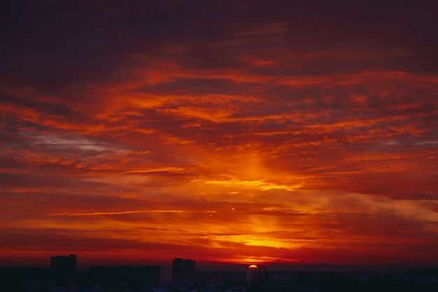 Pejzaż z żywym, ognistym świtem. niesamowite ciepłe dramatyczne pochmurne niebo nad ciemnymi sylwetkami budynków miasta. pomarańczowe światło słoneczne. atmosferyczne tło wschodu słońca w pochmurnej pogodzie. copyspace.