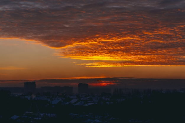 Pejzaż z żywym, ognistym świtem. niesamowite ciepłe dramatyczne pochmurne niebo nad ciemnymi sylwetkami dachów budynków miasta. pomarańczowe światło słoneczne. atmosferyczne tło wschodu słońca w pochmurnej pogodzie. copyspace.