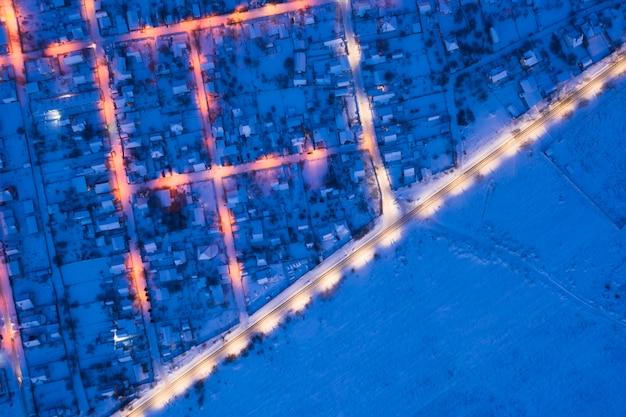 Pejzaż zimowy. oświetlone ulice przedmieść i chałupy.