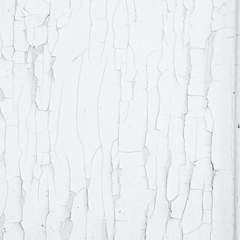 Pękanie i łuszczenie się białej farby na ścianie. vintage tło drewna z łuszczącą się farbą. stara deska z napromienioną farbą