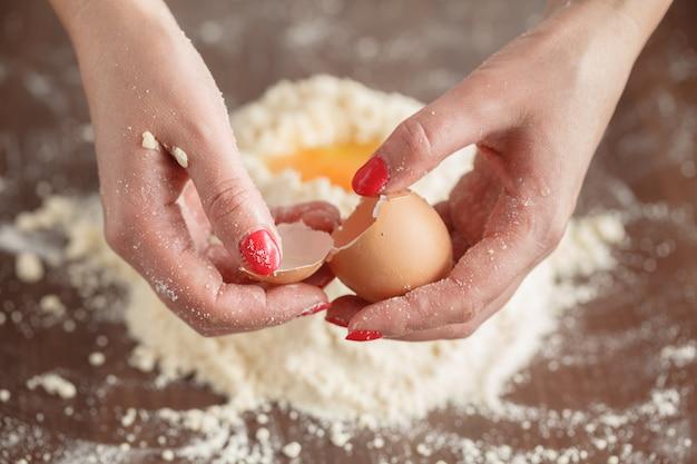 Pękanie jajka i dodawanie do miski.