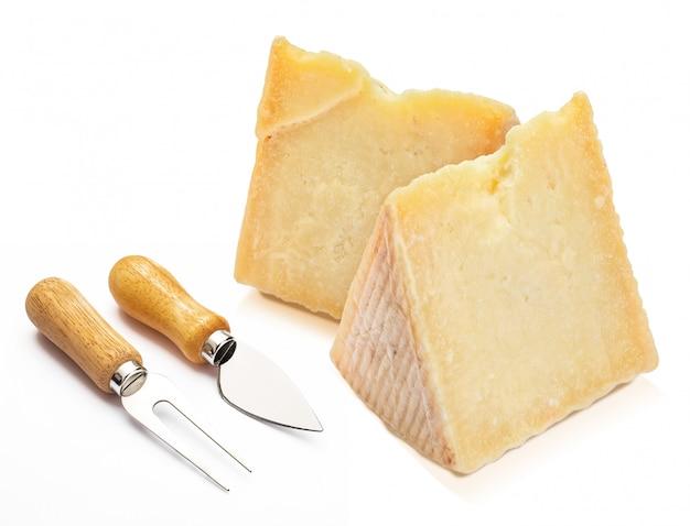 Peklowany ser owczy (typu manchego) w klinie i sztućcach. odosobniony.