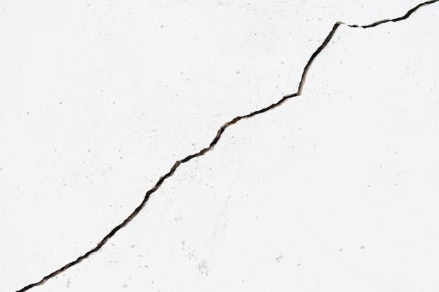 Pęknięcia białej ściany są spowodowane złym osiadaniem terenu budynku.