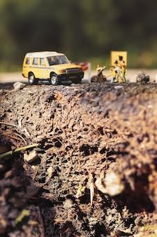 Pęknięta asfaltowa droga i roboty drogowe z miniaturowymi figurkami w wiejskim otoczeniu. miękka ostrość i niewielka głębia ostrości.