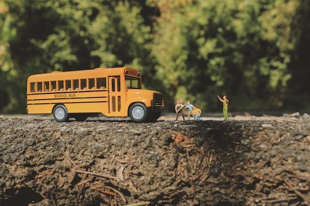 Pęknięta asfaltowa droga i roboty drogowe z miniaturowymi figurkami w wiejskim otoczeniu.